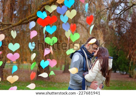 couple kissing in the park, decoration background of hearts of paper, Valentines Day.