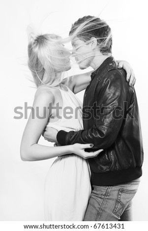 Couple kissing in the wind, studio shot - stock photo