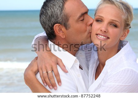Couple kissing on a beach - stock photo