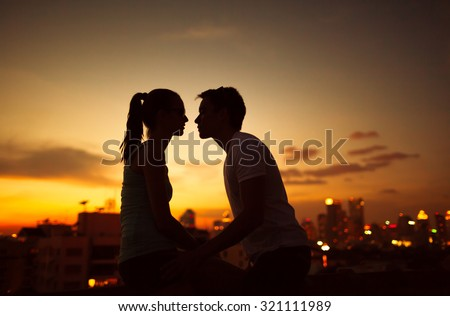 Couple kissing on a city roof top.  - stock photo