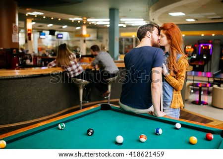 Couple kissing on a date in a snooker bar - stock photo