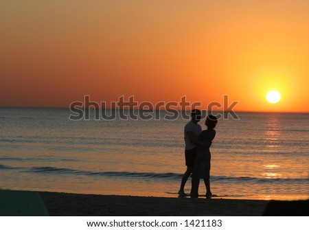 Couple kissing on the Beach at sunset. - stock photo