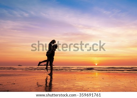 Couple kissing on the beach with a beautiful sunset in background, man lifting the woman - stock photo