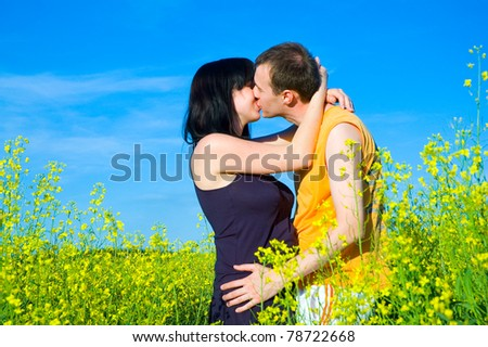 couple kissing on the field - stock photo