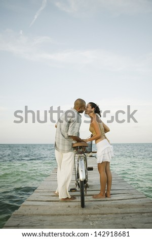 Couple kissing over a bike on a pier