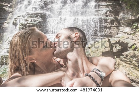 Couple kissing passionately with waterfall background. pov selfie view