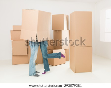 couple kissing under box during moving house - stock photo
