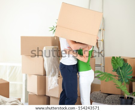 couple kissing under the box during moving house - stock photo