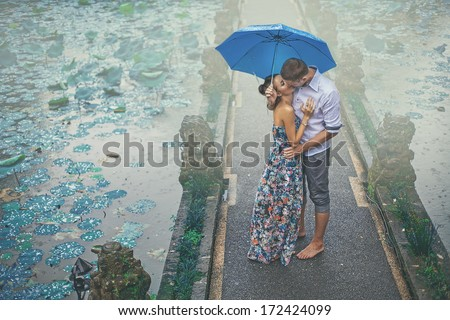 couple kissing under the rain on their first date - stock photo