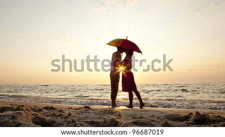 Couple kissing under umbrella at the beach in sunset. - stock photo