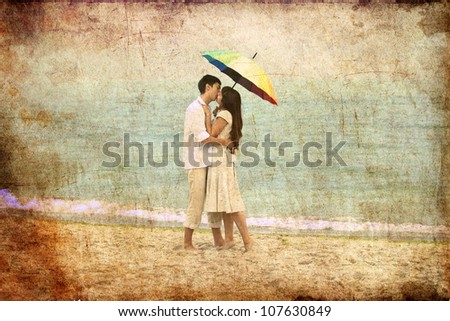 Couple kissing under umbrella at the beach. Photo in old image style. - stock photo