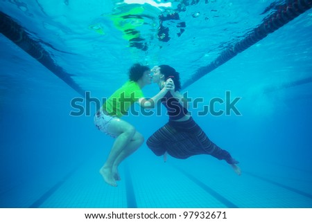 Couple kissing underwater in the pool - stock photo