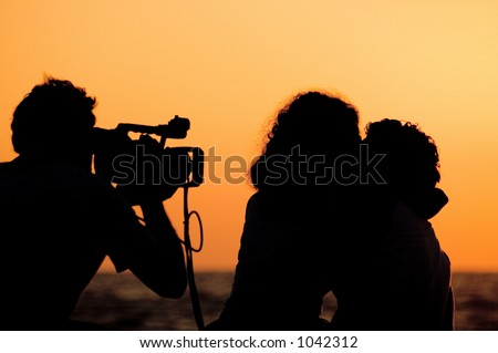 Couple kissing while filming romantic movie