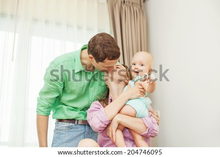 Couple kissing white holding their baby (focus on the eyes of baby) - stock photo