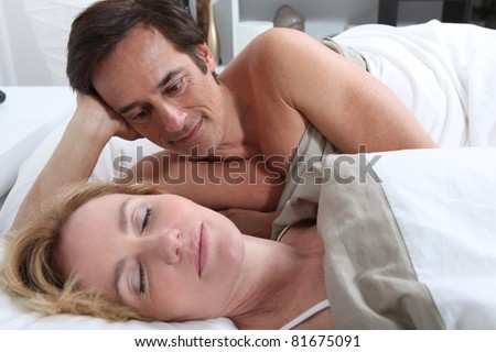 Couple laid in bed together - stock photo