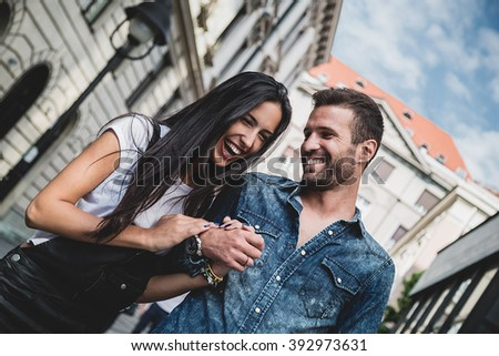 Couple laughing and holding hands in the city - stock photo