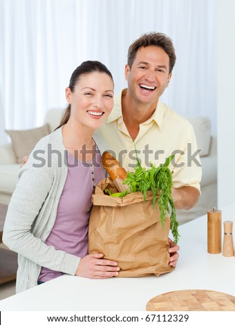 Couple laughing standing in the kitchen with shopping bags full of vegetables