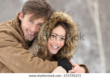 Couple laughing with a perfect smile and white teeth and looking at camera in winter holidays - stock photo