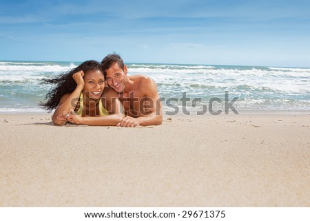 Couple laying at beach on sand, having fun - stock photo