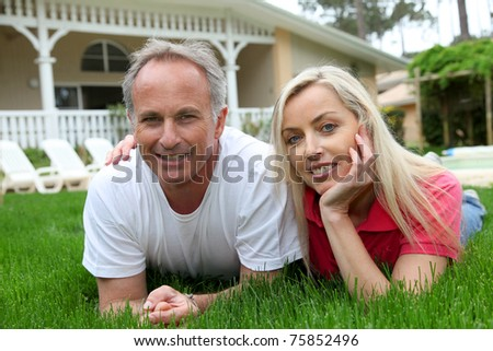 Couple laying down in house garden - stock photo