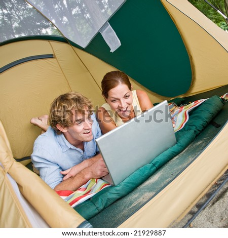 Couple laying in tent using laptop - stock photo