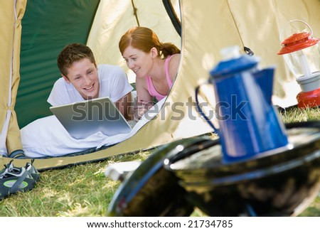 Couple laying in tent with laptop - stock photo