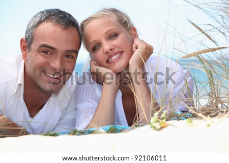 Couple laying on a beach - stock photo