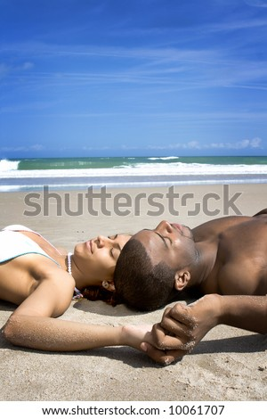 Couple laying on a beach. Blue sky in the background.