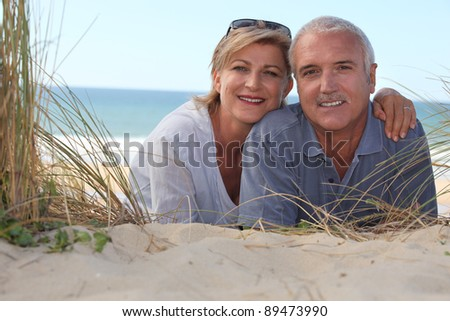 Couple laying on beach - stock photo