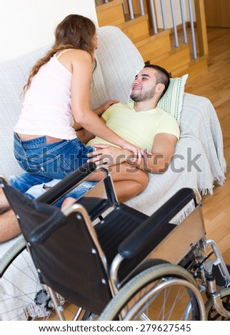 Couple laying on couch near wheelchair in home interior