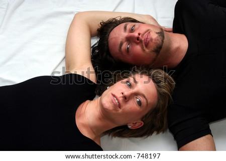 Couple laying on white - stock photo