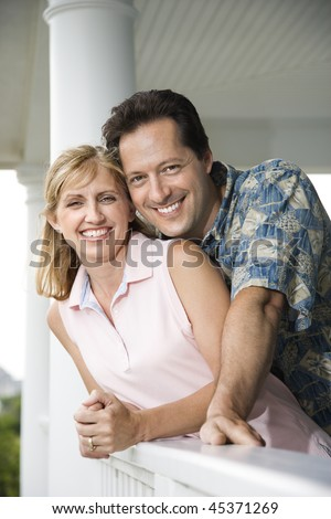 Couple lean on a house porch railing smiling towards the camera. Vertical shot. - stock photo