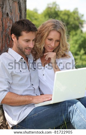 couple leaning on tree with laptop