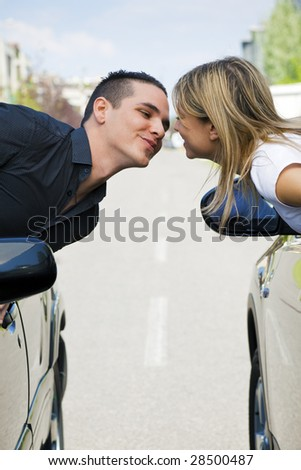couple leaning out of car windows and kissing. Copy space - stock photo