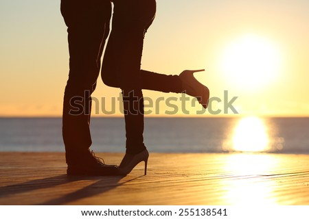 Couple legs silhouette hugging in love on the beach with the sun in the background at sunset