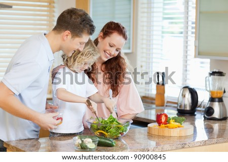 Couple letting their young child stir the salad - stock photo