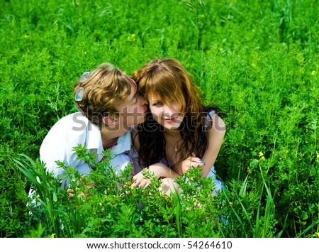 Couple lie in a green grass - stock photo