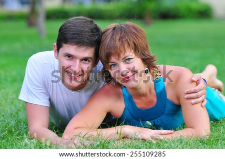 couple lie on the grass - stock photo