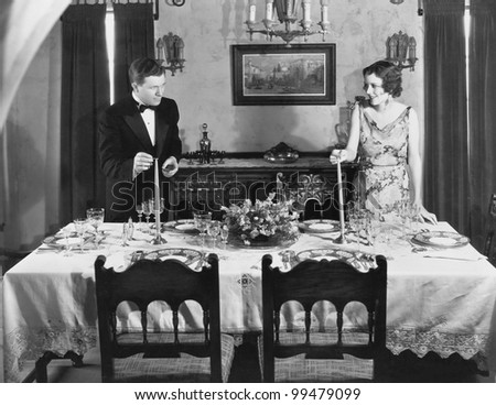 Couple lighting candles on table set for dinner