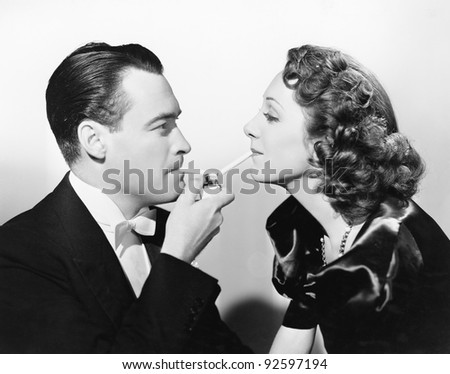 Couple lighting two cigarettes at once with a cigarette lighter - stock photo