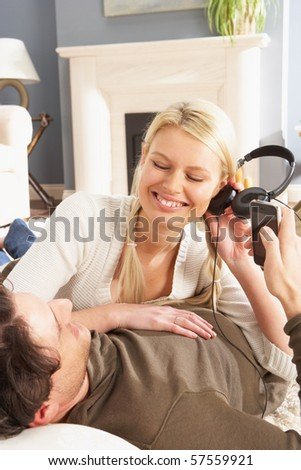 Couple Listening To MP3 Player On Headphones Relaxing Laying On Rug At Home - stock photo