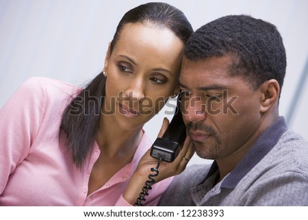 Couple listening to news over the telephone at home - stock photo