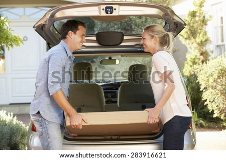 Couple Loading Large Package Into Back Of Car - stock photo