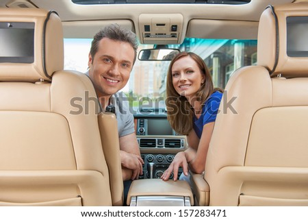 Couple look on the back seat while smiling  - stock photo