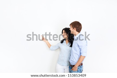 couple look side point finger to empty copy space, at white wall new house, apartment, young man and woman