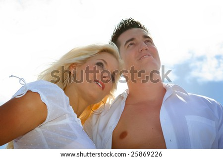 Couple looking ahead opposite blue sky. - stock photo