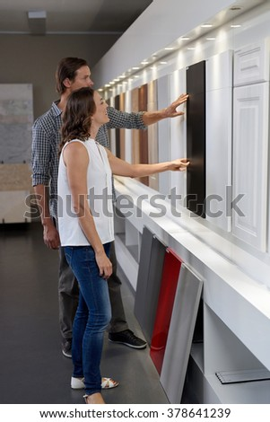 Couple looking and touching different materials and samples in contemporary kitchen shop showroom while designing their dream kitchen renovating their home - stock photo
