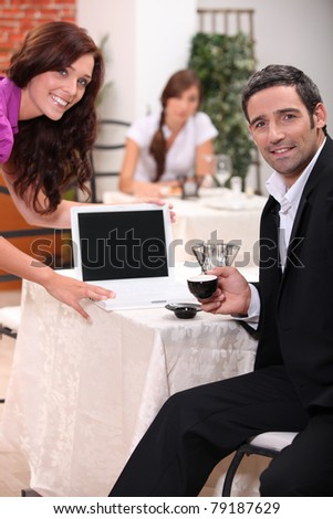 Couple looking at a blank computer screen in a restaurant - stock photo