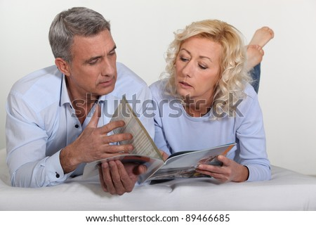 Couple looking at a catalog - stock photo