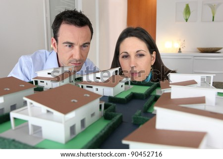 Couple looking at a model of a housing estate - stock photo